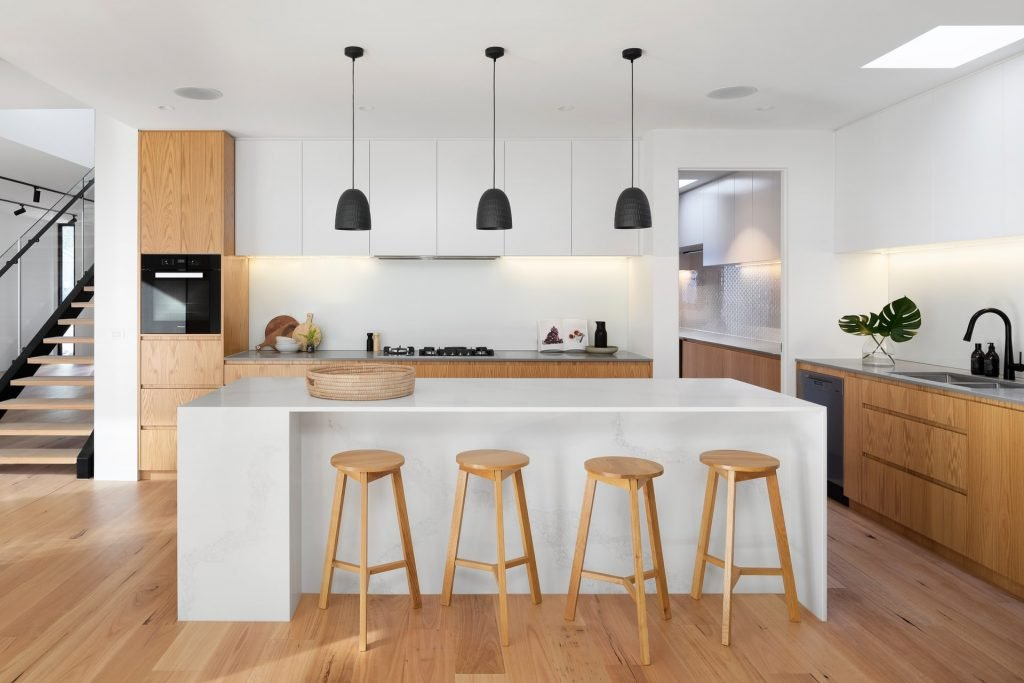 This unbroken white splashback is part of a Melbourne kitchen renovation. It looks clean, seamless, and effortlessly chic